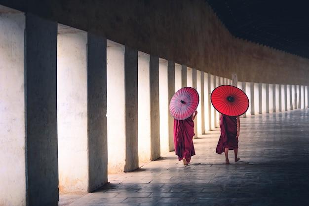Principiante da monge dois budista que guarda guarda-chuvas vermelhos e que anda no pagode, myanmar. Foto Premium