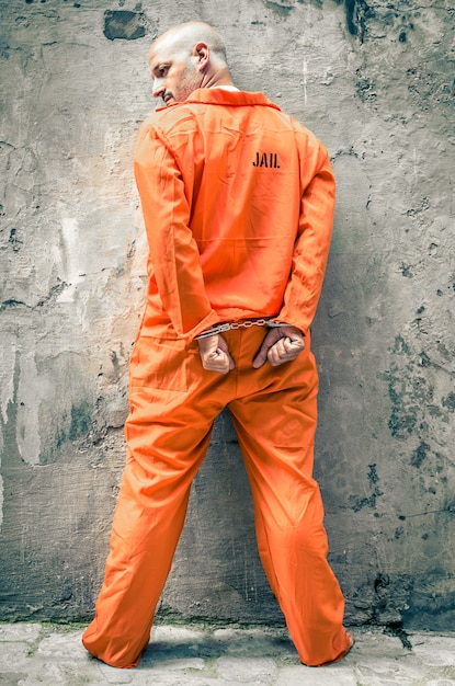 Prisioneiro com algemas na parede da prisão Foto Premium