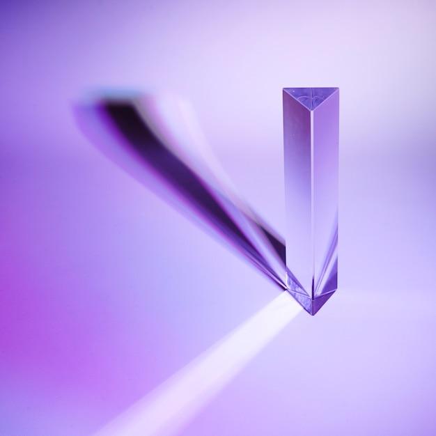 Prisma de cristal com sombra escura no fundo roxo Foto gratuita