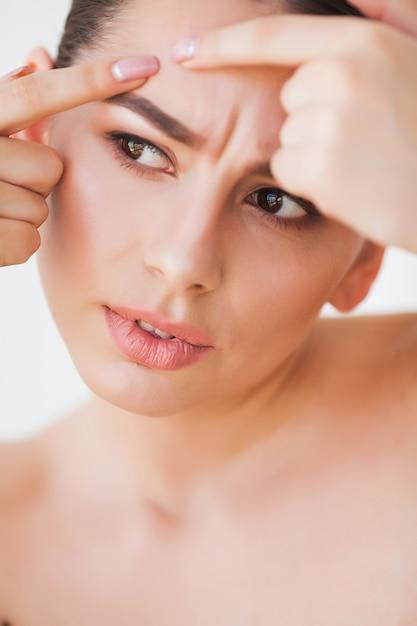Problema de pele. mulher esmagando o ponto no rosto e olhando no espelho Foto Premium