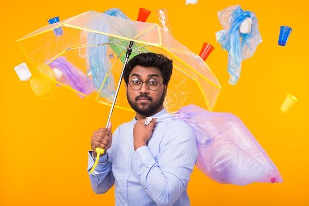 Problema de reciclagem de plástico, conceito de ecologia e desastre ambiental - homem indiano se escondendo do lixo sob um guarda-chuva na parede amarela Foto Premium