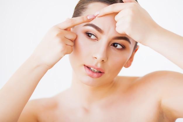 Problema pele. mulher, esmagando o local no rosto e olhando no espelho Foto Premium
