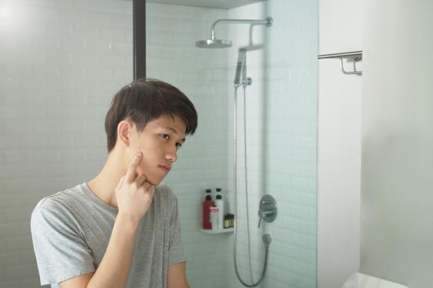 Problemas de pele adolescente, jovem é olhar para o espelho e segurando o próprio rosto no banheiro. Foto Premium