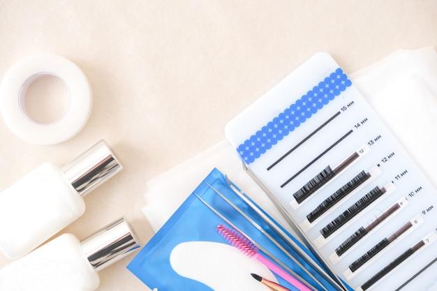 Procedimento de extensão de cílios. ferramentas. cola, pinças, pincéis. salão de beleza, moda e mulher compõem o conceito Foto Premium