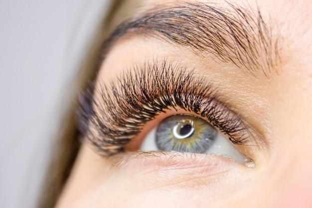 Procedimento de extensão dos cílios. olho de mulher com cílios longos e falsos. beleza e moda Foto Premium