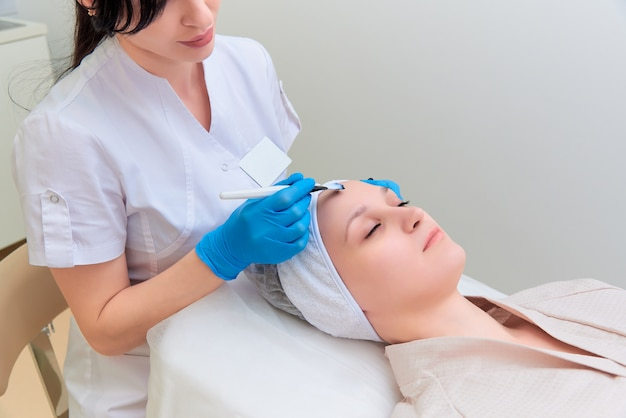 Procedimento de peeling facial com carbono na clínica de cosmetologia a laser. Foto Premium