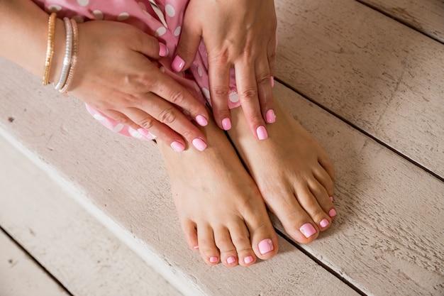 Procedimento de spa do prego. manicure e pedicure. mãos e pés femininos no chão de madeira. resultado do procedimento de salão de spa. cuidados com o corpo, tratamentos de spa. esmaltes e acessórios. mulher elegante. Foto Premium