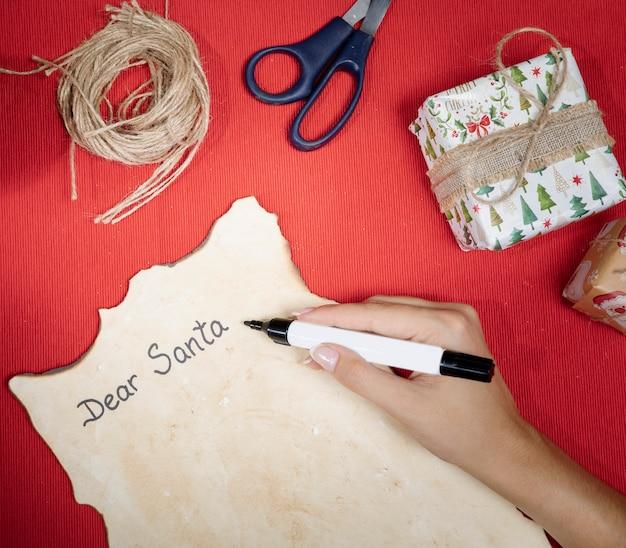 Processo de alto ângulo para escrever uma carta para o papai noel Foto gratuita
