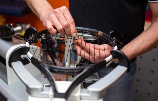 Processo de amarrar uma raquete de tênis em uma loja de tênis, conceito de esporte e lazer Foto Premium