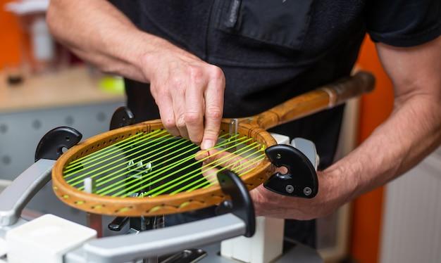 Processo de amarrar uma raquete de tênis histórica ou retro em uma loja de tênis, conceito de esporte e lazer Foto Premium