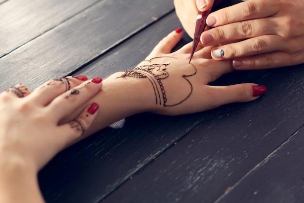 Processo de aplicação de mehndi nas mãos femininas Foto Premium