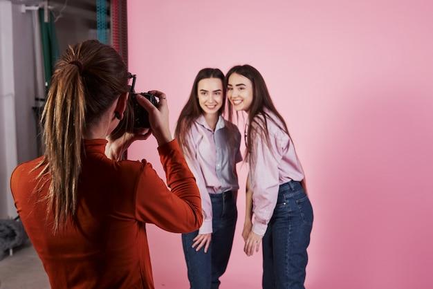 Processo de captura. foto de duas garotas que fotografaram pelo operador de câmera feminino no estúdio Foto gratuita