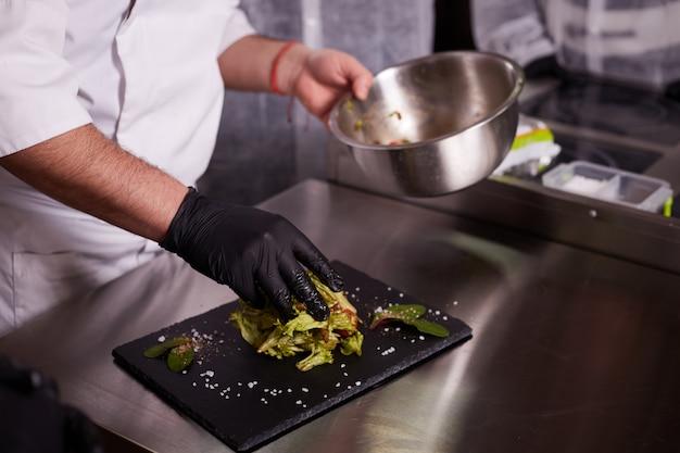 Processo de cozinhar salada quente com vitela. mãos de um chef em luvas pretas. placa de ardósia preta. Foto Premium