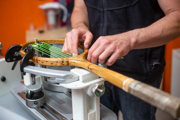 Processo de enfileiramento de uma raquete de tênis em uma loja de tênis, conceito de esporte e lazer, manutenção e tunning de raquete de tênis Foto Premium
