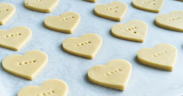 Processo de fazer biscoitos em forma de coração com a palavra amor prontos para assar. conceito de pastelaria. Foto Premium