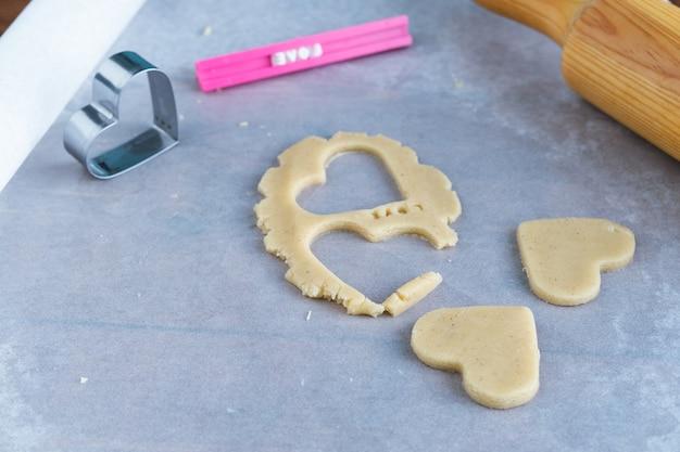 Processo de fazer biscoitos em forma de coração. conceito de pastelaria romântica. Foto Premium