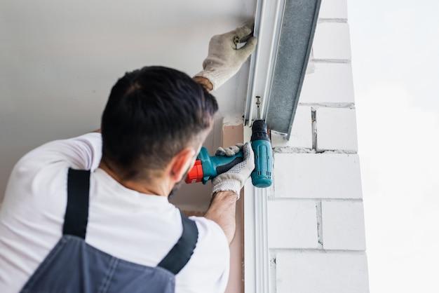 Processo de homem usando a chave de fenda. trabalhador faz a instalação da janela Foto Premium