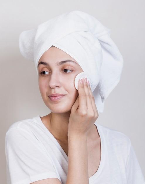 Processo de limpeza de rosto de mulher bonita Foto gratuita