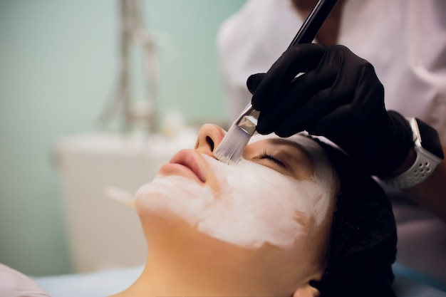 Processo de massagem de máscara cosmética e tratamentos faciais no salão de beleza Foto Premium