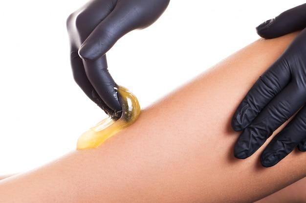 Processo de remoção de pêlos na perna feminina com depilação Foto Premium