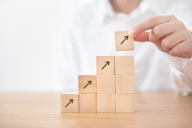 Processo do sucesso do crescimento do conceito do negócio, mão da mulher de negócios que arranja o cubo de madeira que empilha como a escada da etapa com a seta acima do símbolo. Foto Premium