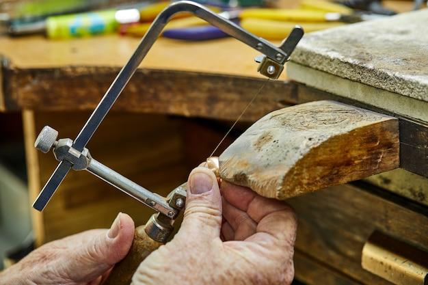 Produção de joias. joalheiro usando serra para criar jóias Foto Premium