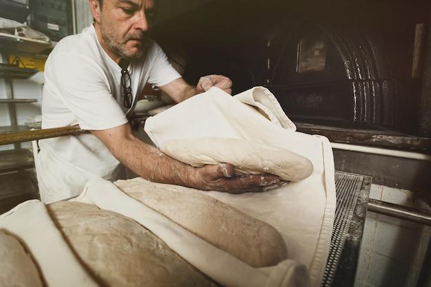 Produção de pão assado com forno de lenha em padaria Foto Premium