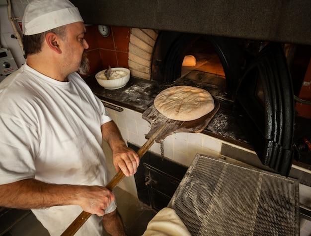 Produção de pão assado com forno de lenha em uma padaria. Foto Premium