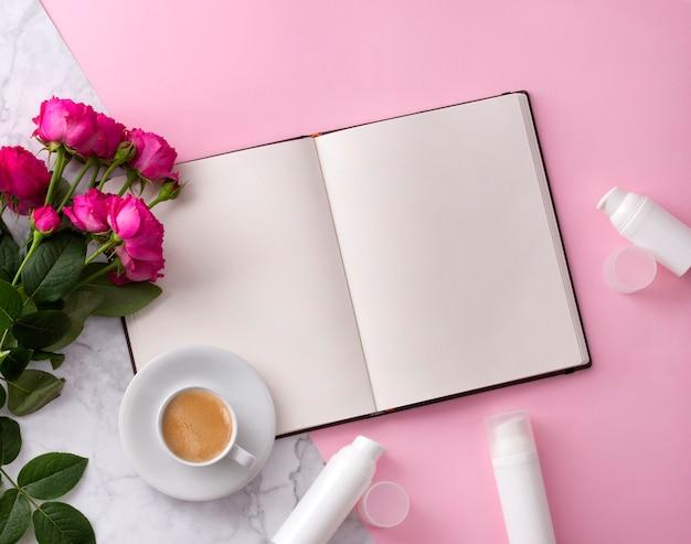 Produto cosmético para cuidados com a pele, caderno aberto, café e flores em rosa Foto Premium