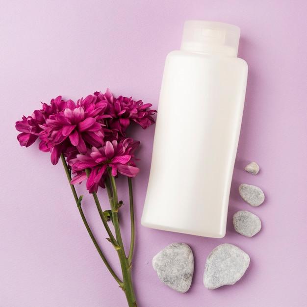 Produto de cosméticos branco com pedras rosa flor e spa em fundo rosa Foto gratuita