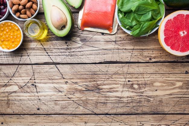 Produtos antioxidantes do alimento saudável do conceito: peixes e óleo do abacate, das porcas e de peixes, toranja no fundo de madeira. espaço da cópia Foto Premium
