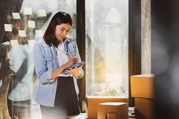 Produtos asiáticos da verificação da mulher no estoque com intenção e feliz. Foto Premium