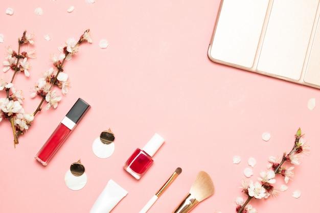 Produtos cosméticos, brincos, bolsa em um fundo rosa. vista plana leiga Foto Premium