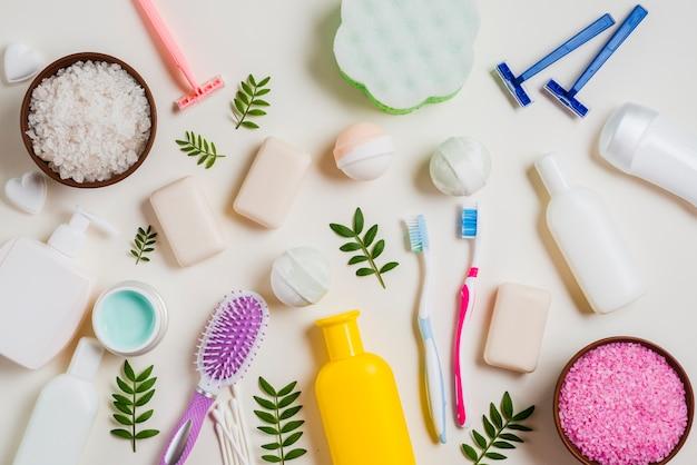 Produtos cosméticos com sal; escova dental; navalha; escova de cabelo e folhas no pano de fundo branco Foto gratuita