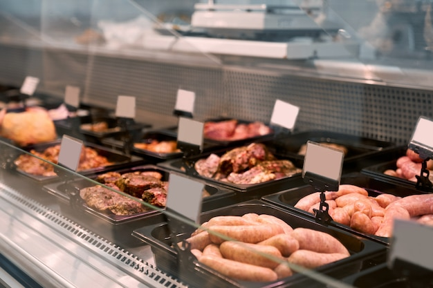 Produtos de carne crua no balcão de vidro. Foto gratuita