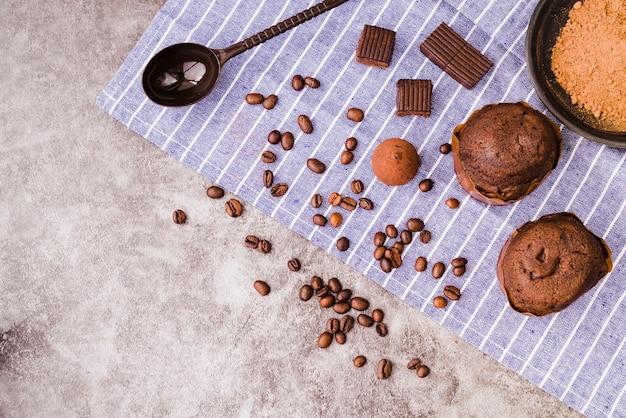 Produtos de chocolate e ingredientes no guardanapo sobre o pano de fundo concreto Foto gratuita