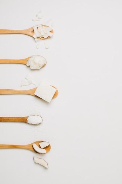Produtos de coco em colheres de madeira com espaço para texto Foto gratuita