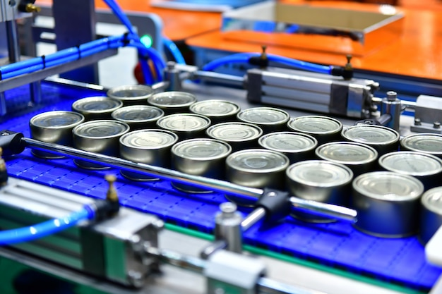 Produtos de conservas alimentares na correia transportadora no armazém de distribuição conceito de sistema do transporte das espigas. Foto Premium