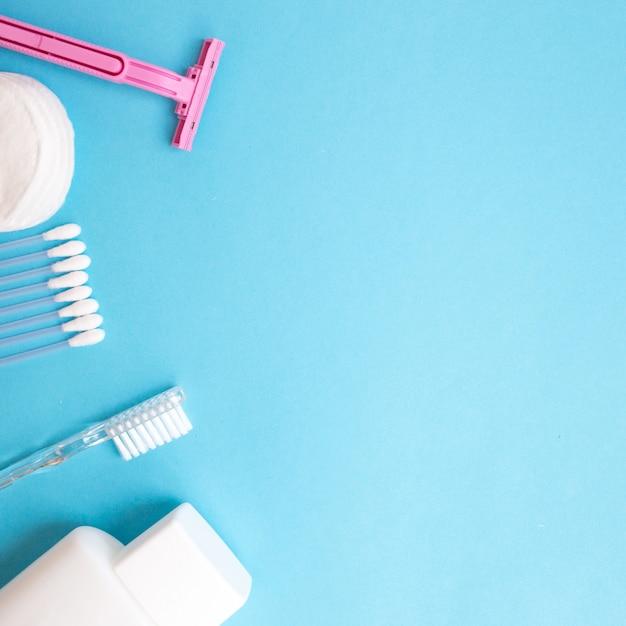 Produtos de cuidado pessoal. garrafa branca, navalha, varas de orelha, almofadas de algodão, escova de dentes em azul b Foto Premium