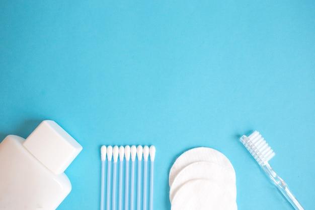 Produtos de cuidado pessoal. garrafa branca, palitos de orelha, almofadas de algodão, escova de dentes em azul backgrou Foto Premium