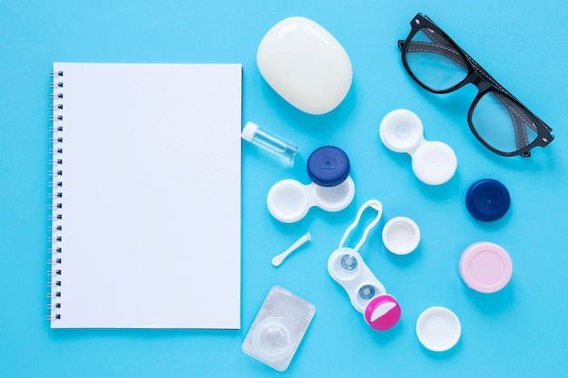 Produtos de cuidados com os olhos em fundo azul com maquete de notebook Foto gratuita