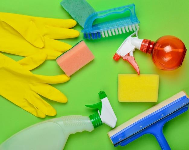 Produtos de limpeza doméstica. esfregona, esponja, frasco de spray, luvas de látex amarelas, pincel. vista do topo. estilo liso leigo Foto Premium