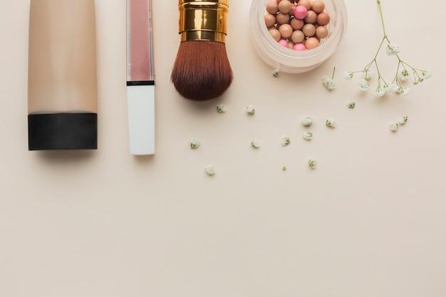 Produtos de maquiagem de vista superior alinhados na mesa Foto gratuita