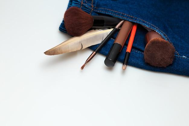 Produtos de maquiagem e produtos de beleza cosméticos derramando fora de jeans de mulher Foto Premium