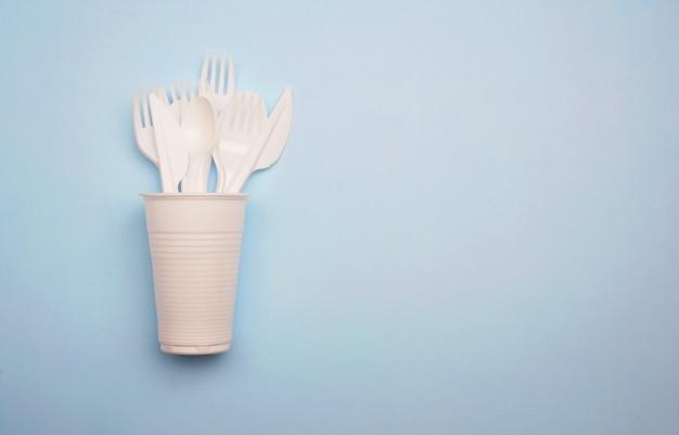 Produtos de uso único de plástico: talheres de plástico, copos em fundo azul brilhante Foto Premium