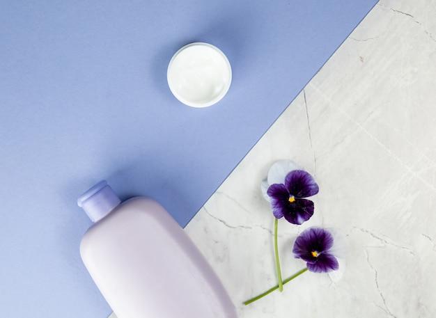 Produtos para cuidados com o corpo e flores em azul Foto Premium