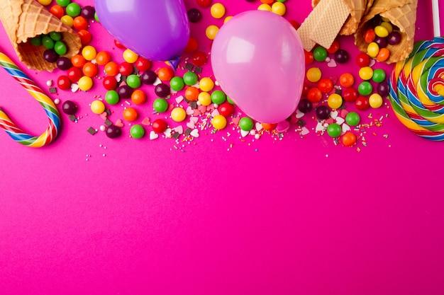 Produtos saborosos e festivos sobre o fundo rosa brilhante Foto gratuita