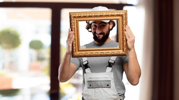 Profesional pintor segurando uma moldura barroca Foto Premium