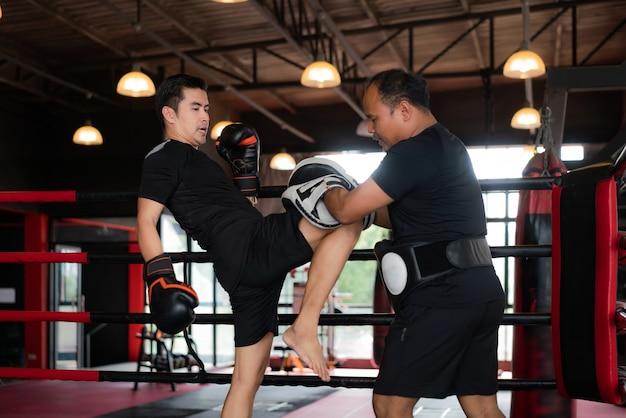 Professional asian kick boxer strike com o joelho direito ao treinador profissional no estádio de boxe. Foto Premium