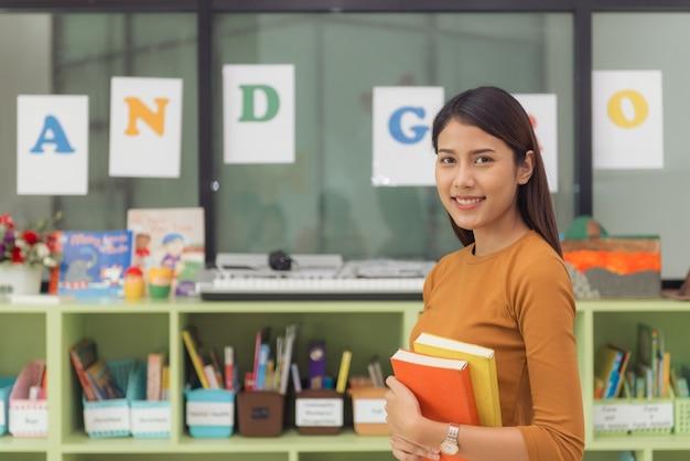 Professor asiático bonito sorrindo para a câmera na parte de trás da sala de aula na escola primária. imagens de estilo de efeito vintage. Foto gratuita